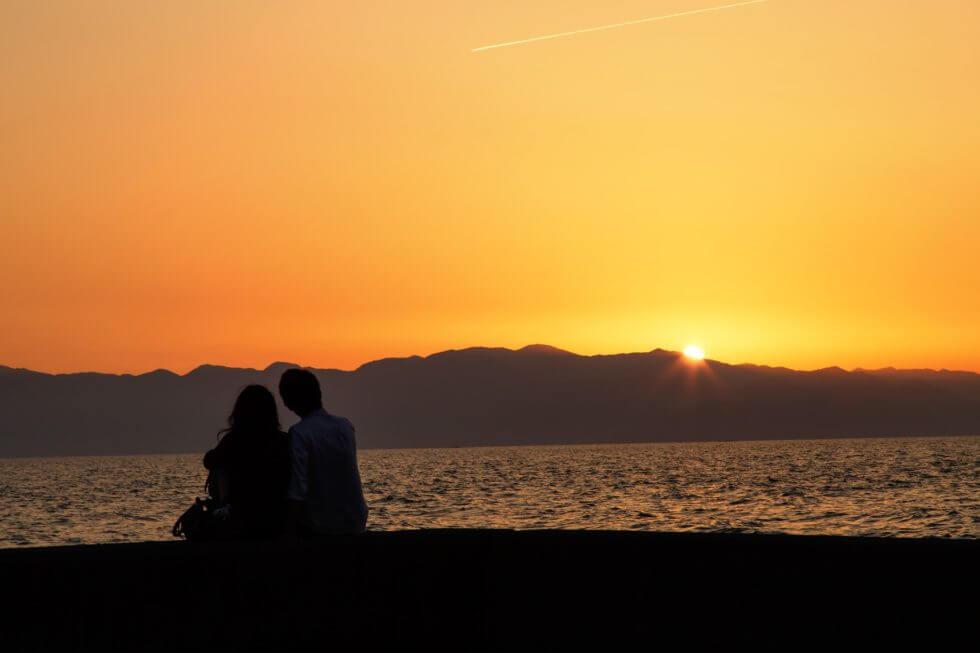 カップルが夕暮れに二人で浜辺にいる画像