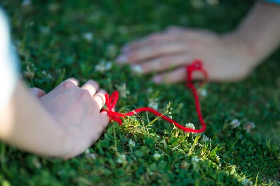 二人の指が赤い糸で結ばれている画像