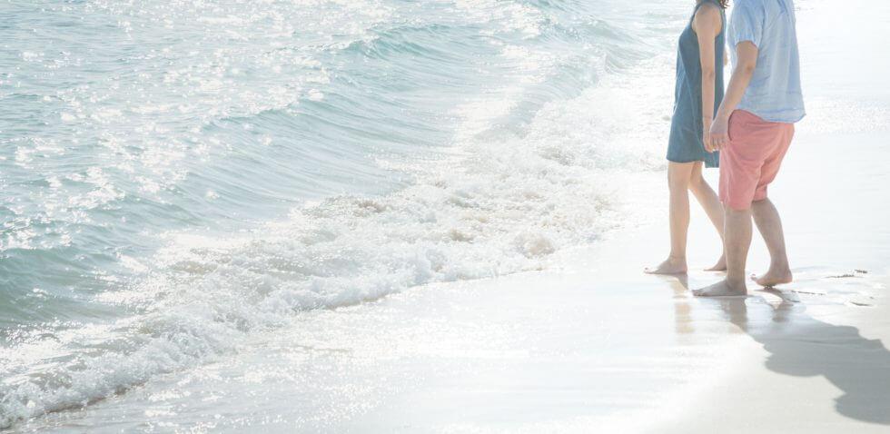 波打ち際で歩いているカップル