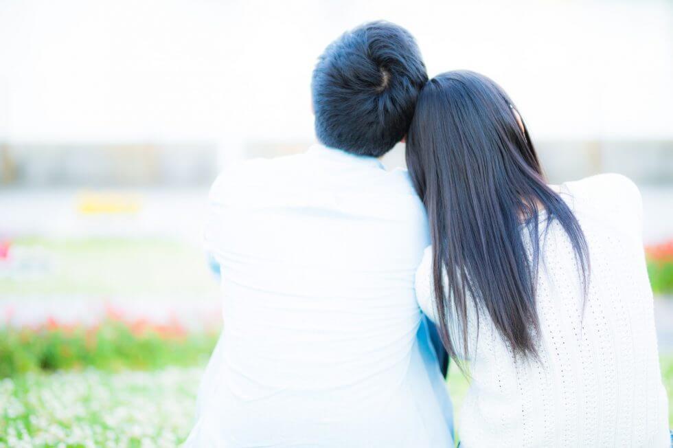 公園に座りながらお互いに身を寄せ合うカップル