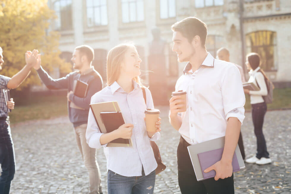 The guy and the girl are standing together in the courtyard of the university. They are students. The sun shines brightly on the street. Nearby their friends.