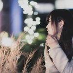 夜の街で誰かを待つ女性