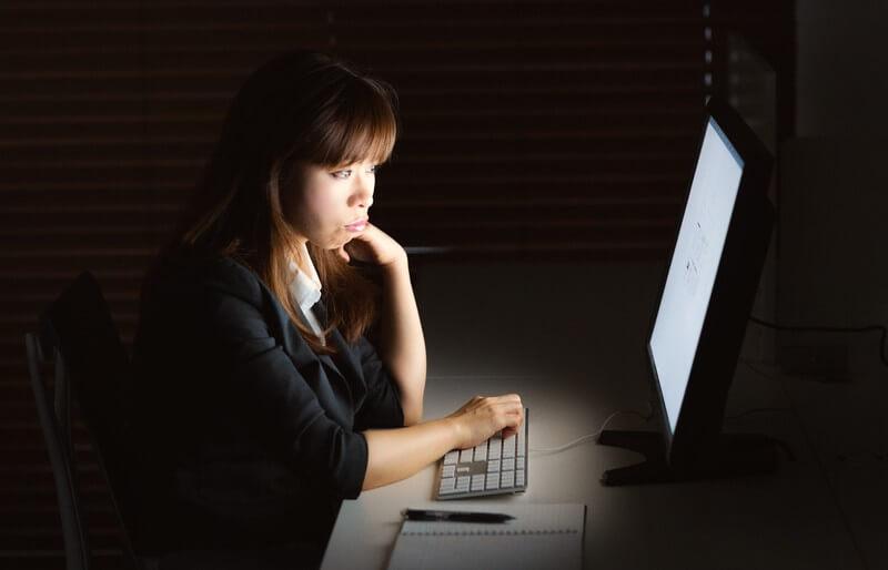 電気が消されてもなお残業を続ける女性