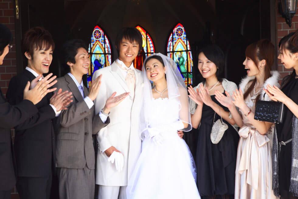 結婚式で友人に祝われる新婚夫婦