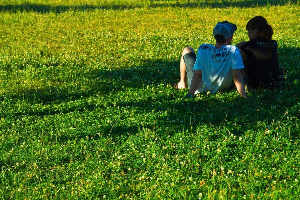 芝生で語り合うカップル