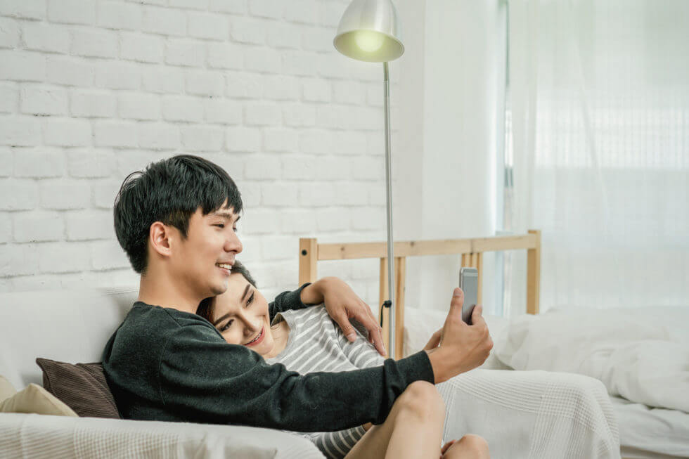 Happy Asian Lover sitting and using the digital smart mobile phone to selfie over the sofa of living room at modern home, Couple successfull and lifestyle concept