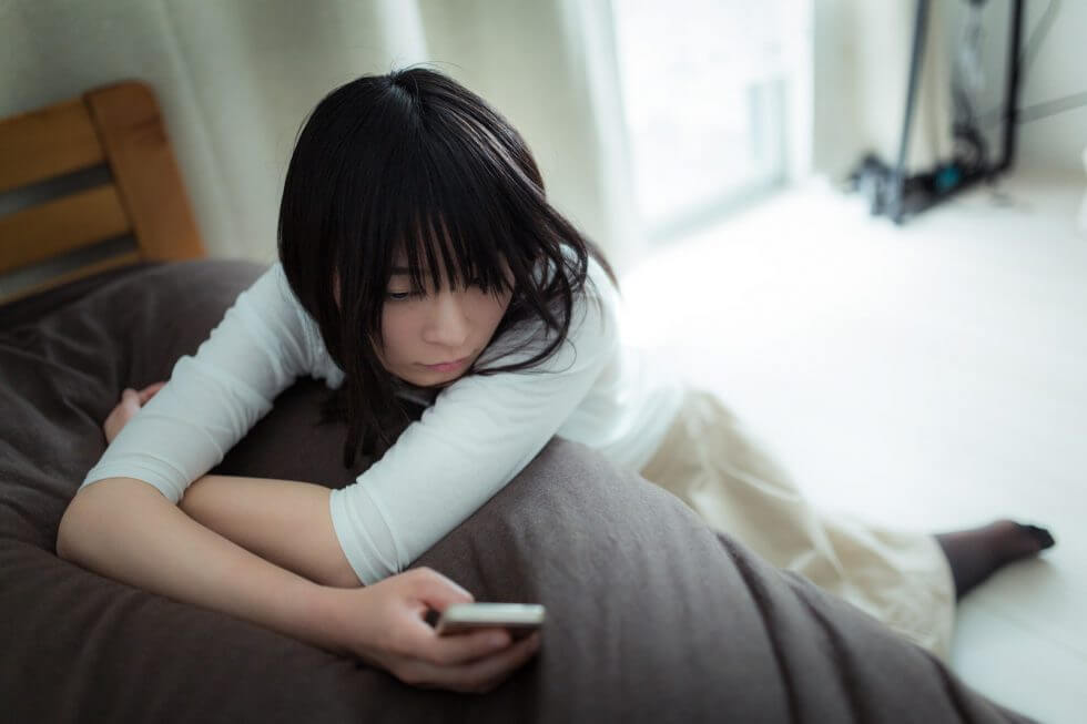 携帯電話を見つめて悩んでいる女性の画像