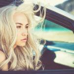 走行中の車内から髪をなびかせ景色を眺める女性