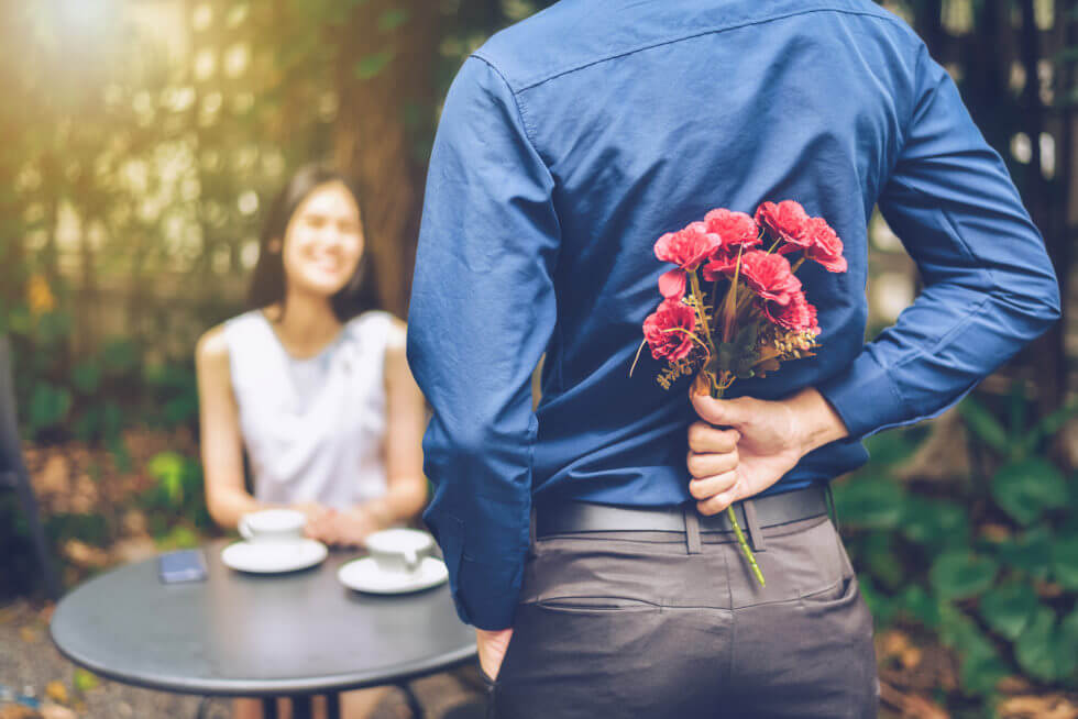 The man is hiding red flowers behind him in order to surprise his girlfriend.